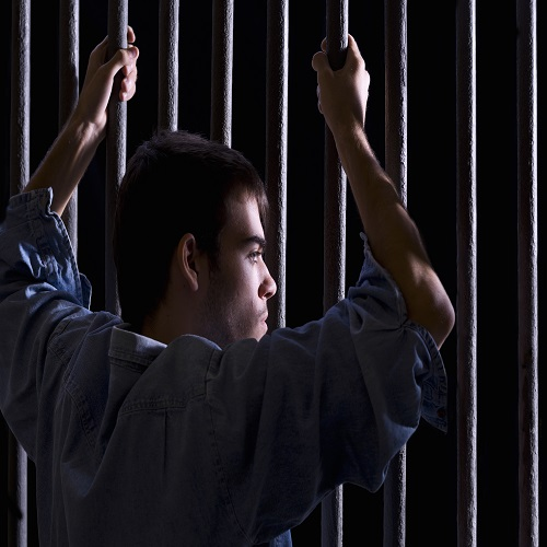 Imprisoned man, looking down, seized to a few bars