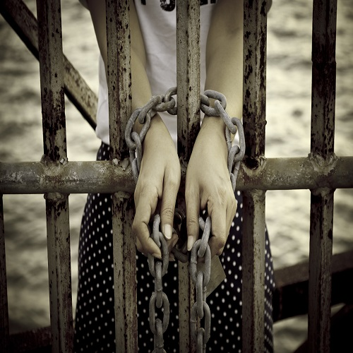 hands tied with rusty chain behind the bars
